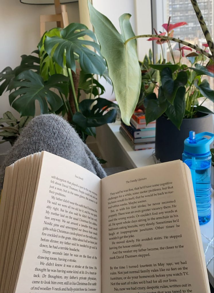 Image shows an open book and lots of plants in the background